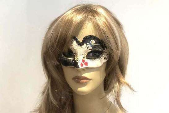 small masquerade mask with heart decoration shown on female face