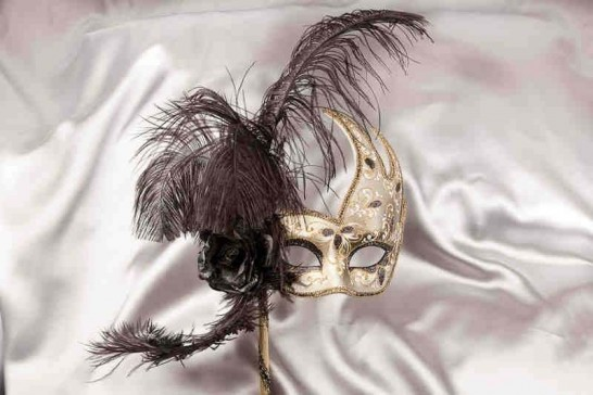 black and gold feathered mask on stick