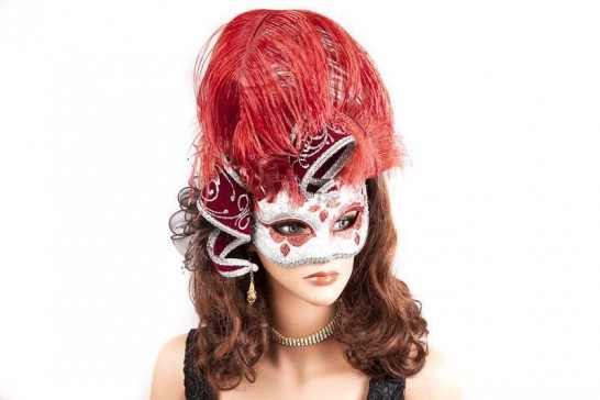 Red jolly jester and feather masquerade mask on female face