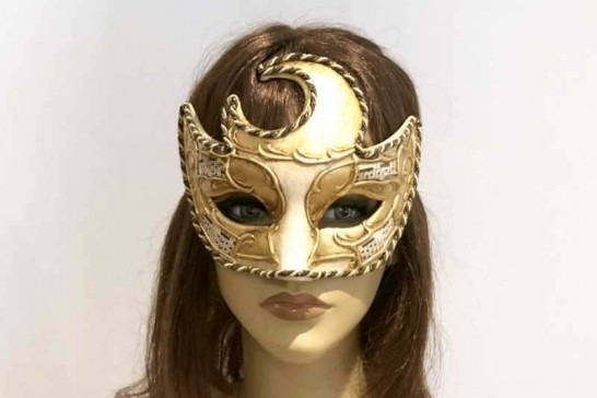 Moon shaped masquerade mask in gold and cream shown on female face