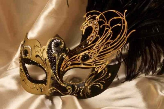 Paper mache Venetian mask with filigree detail and luxury tall feathers in gold and black close up view