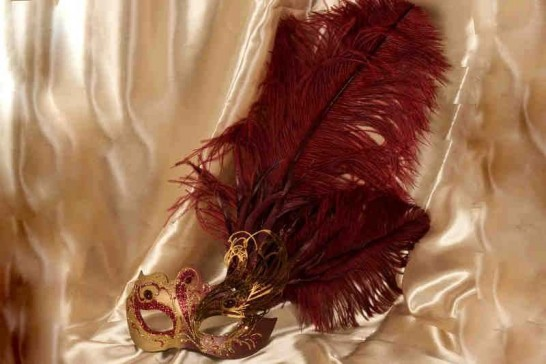 red and gold custom Venetian masks with filigree detail and tall feathers