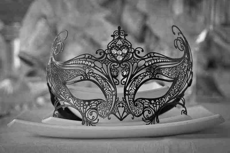 Filigree metal mask on table as place setting
