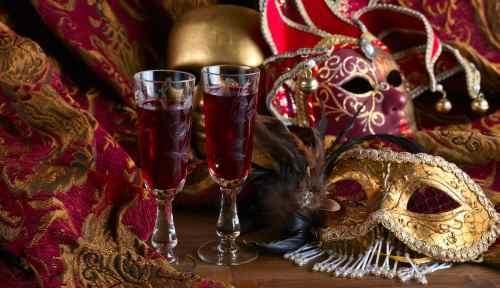 three masks on cushion with glass of sherry