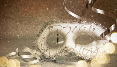 White masquerade mask placed on a mirror with ribbon