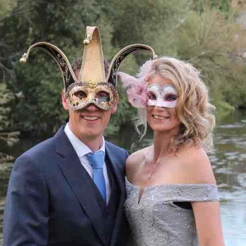 Man wearing jester mask with lady in pink feather mask